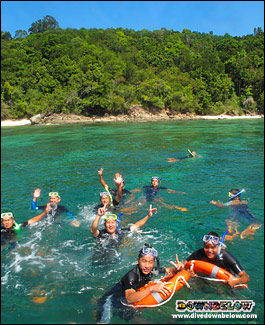 Happy snorkelers above a coral reef in clear water