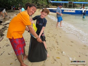 Alvin holds the trash bag for one of the Australian International School kids