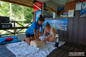 Divemaster Jessica assists Sam to resuscitate dummy victim Annie during the Emergency Oxygen Provider course