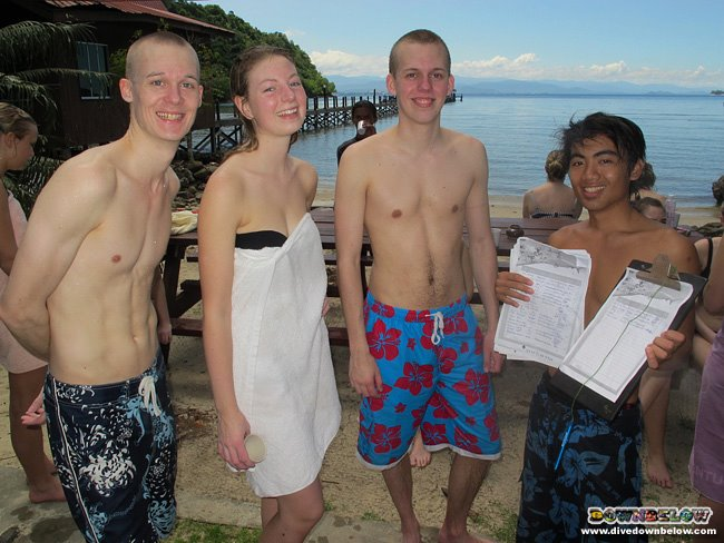 Local Divemaster Intern Victor (far right) explains the peril sharks are in to our adventurers from Denmark