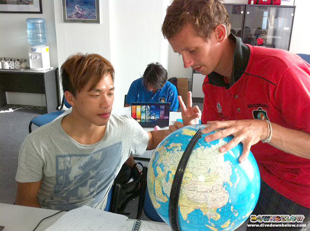 PADI IDC Staff Instructor Paul on the right, gives Kenji a demo in training aid use.