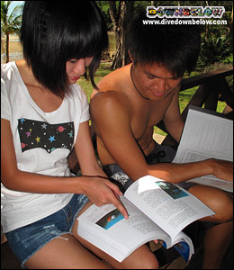 Student divers studying the dive manuals for the theory portion of becoming a diver